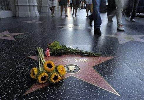 Поклонники несут цветы к звезде Патрика на Аллее славы. Фото: АП.