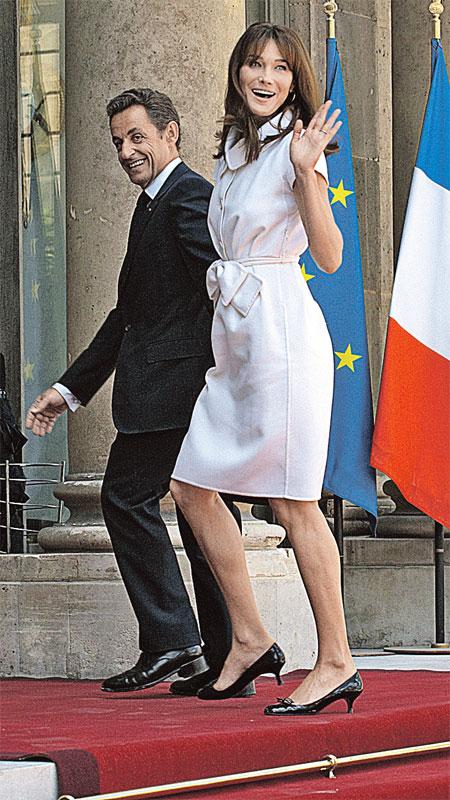Несмотря на массивные каблуки своих ботинок, Саркози рядом с супругой Карлой выглядит почти карликом.