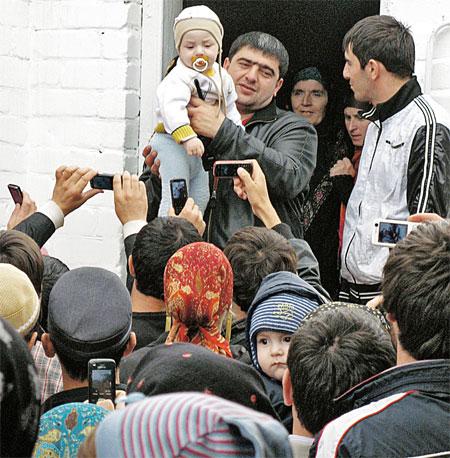 Все паломники хотят подержать малыша, но остается довольствоваться лишь снимками на мобильники.