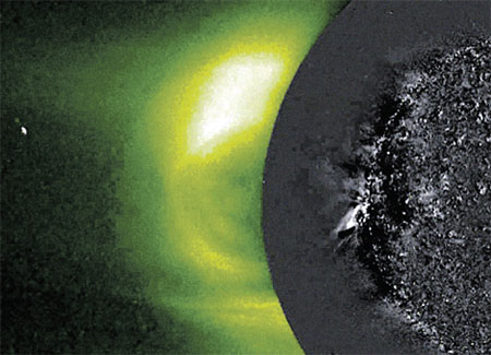 Слева (яркое пятно) - корональный выброс, справа - вызванное им цунами на Солнце (серая «складка» на краю черного пятна).
