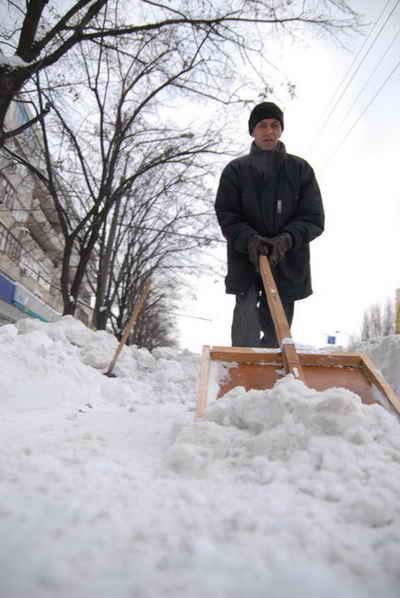 Коммунальщики сгребают снег в кучи, но не вывозят. Фото Ирины МАКУШИНСКОЙ.