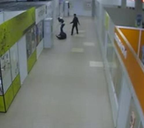 Кадр с камеры наблюдения в супермаркете: Евсюков выстрелил в парня и стал угрожать его девушке.