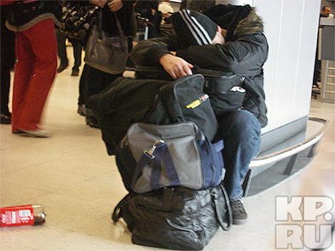Люди в ожидании рейса спят на сумках.