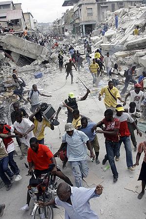 Когда гаитяне идут толпой грабить склад, разогнать их в силах только местному полицейскому с железным прутом. Фото: Анатолий ЖДАНОВ.