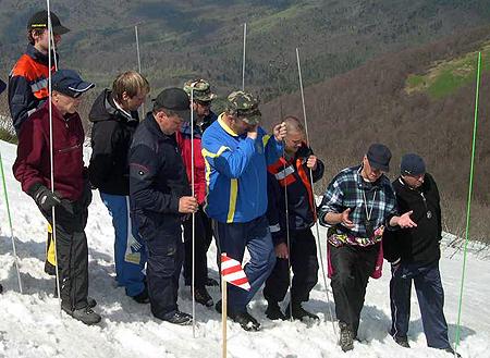 Спасатели ищут своего коллегу под многометровым слоем снега.