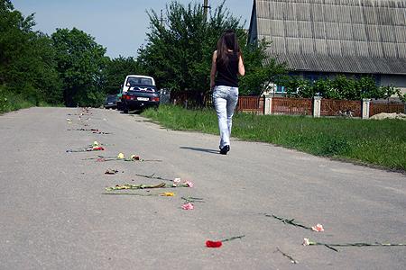Дорога от кладбища к дому семьи погибшей усыпана цветами.