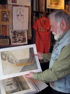 Евгений Путря показывает рисунки своих снов и работы дочери.