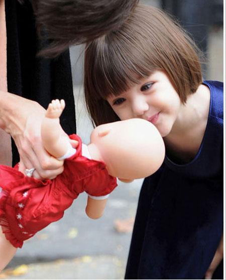 Сури - девочка любознательная, вот только когда ей в куклы играть?. Фото: Wenn.com