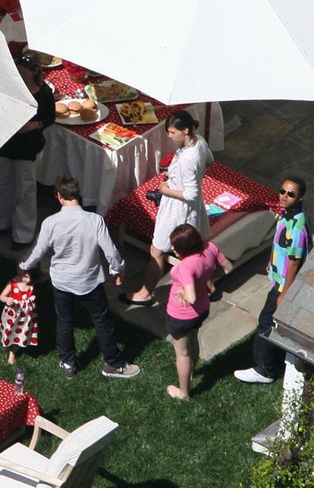 Вечеринка в честь дня рождения Сури на заднем дворе особняка Крузов в Беверли-Хилз. Главные действующие лица: Сури (в платье в горошек), Том Круз (в клетчатой рубашке), Кэти Холмс (в белом платье), приемная дочь Тома Изабелла (в розовой футболке).