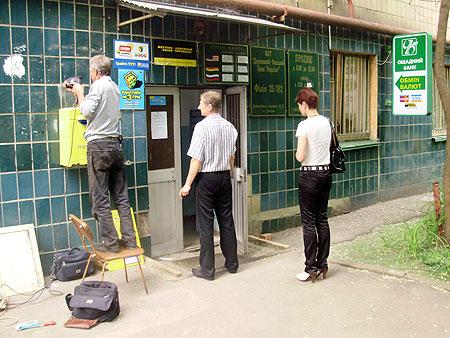 Посетители читают обьявление, что банк уже не работает.