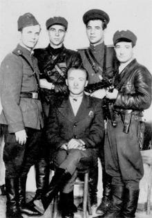 Снимок на память о приезде какого-то крупного оуновца (фамилия и псевдоним не установлены) - он сидит на стуле, на нем добротный пиджак, в кармане авторучка, на ногах хромовые сапоги. Стоят (слева направо) Степан Гуцуляк, Василий Сербенюк и 2 неизвестных