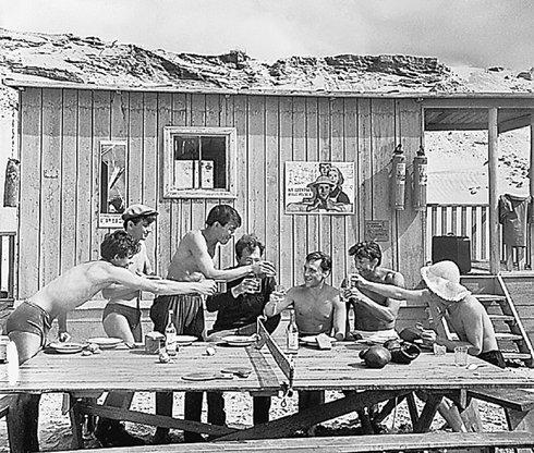 Во время съемок фильма «На завтрашней улице» посиделки устроили прямо на пляже за теннисным столом. 1965 год. Высоцкий, как обычно, в центре компании.