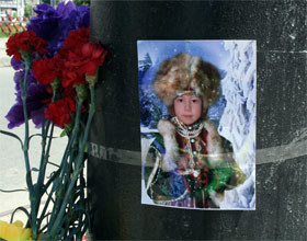 На столбе возле места ДТП висят фото погибших детей, а рядом - цветы и игрушки.