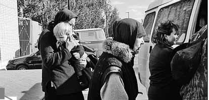 Затворники садятся в «Газель», на которой их повезли в Белоруссию. Инна Вабищевич держит на руках свою дочь Леночку.