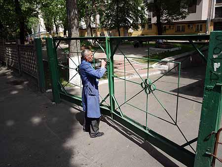 Вахтер Петр Иванович закрывает ворота, через которые мог проехать преступник.