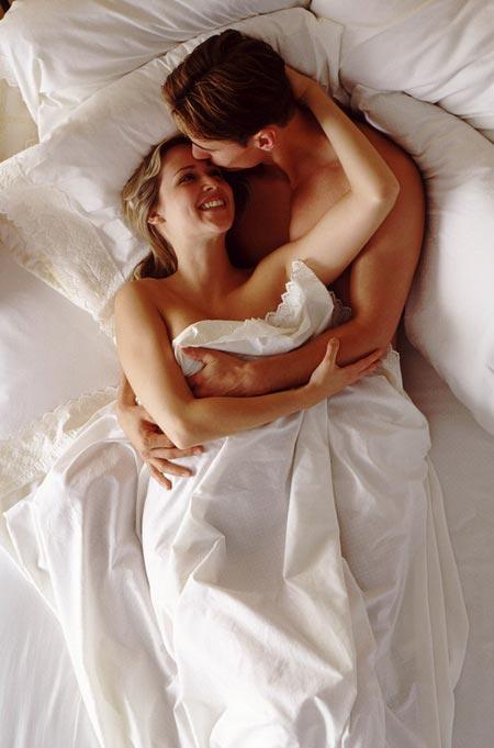Молодая пара в белой постели